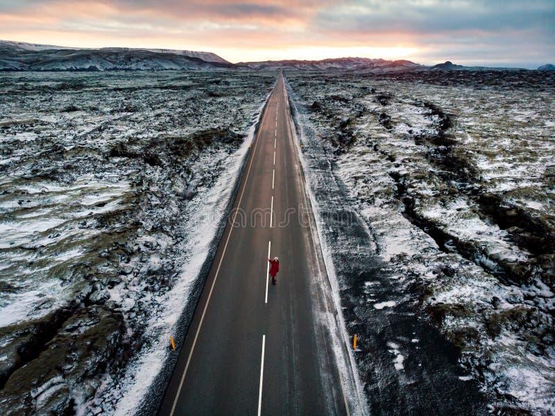 Voyageur féminin sur la route islandaise entourée par des plaines de lave image libre de droits