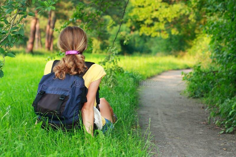 Voyageur fatigué de femme s'asseyant sur l'herbe photo libre de droits