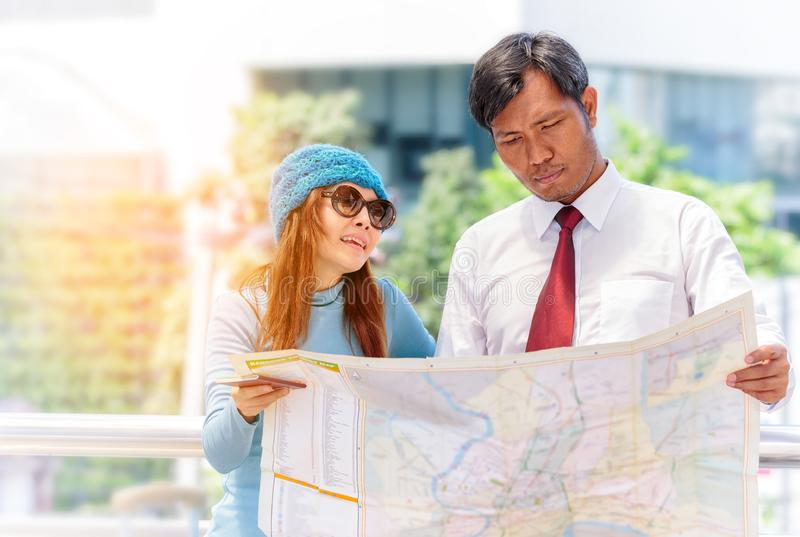 Voyageur heureux de couples avec le bagage regardant le guide de carte dans la ville photos libres de droits