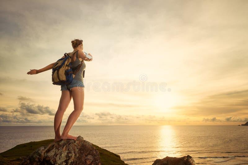 Voyageur heureux insouciant de femme avec le sac à dos appréciant la vue de coucher du soleil photographie stock