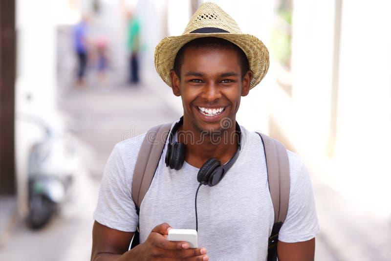 Voyageur heureux marchant dans la ville avec le téléphone portable photographie stock libre de droits