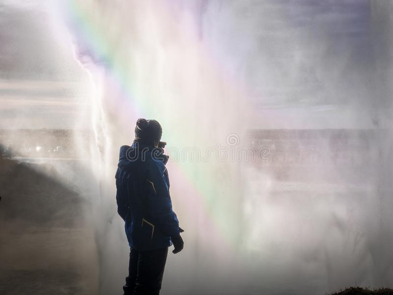 Voyageur masculin derrière la grande cascade en Islande photographie stock