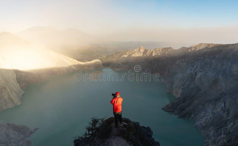 Voyageur prenant la photographie sur le point guidé au lac volcanique Ijen de kawah le matin, l'attraction touristique célèbre et photos stock