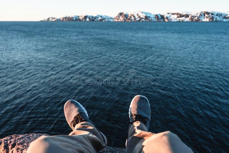 Voyageur s'asseyant sur la falaise devant la rupture au-dessus des montagnes d'océan et de neige photo libre de droits