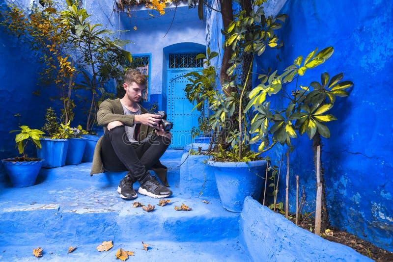 Voyageur s'asseyant sur la rue typique de la vieille Médina dans la ville de Chefchaouen, Maroc photo libre de droits