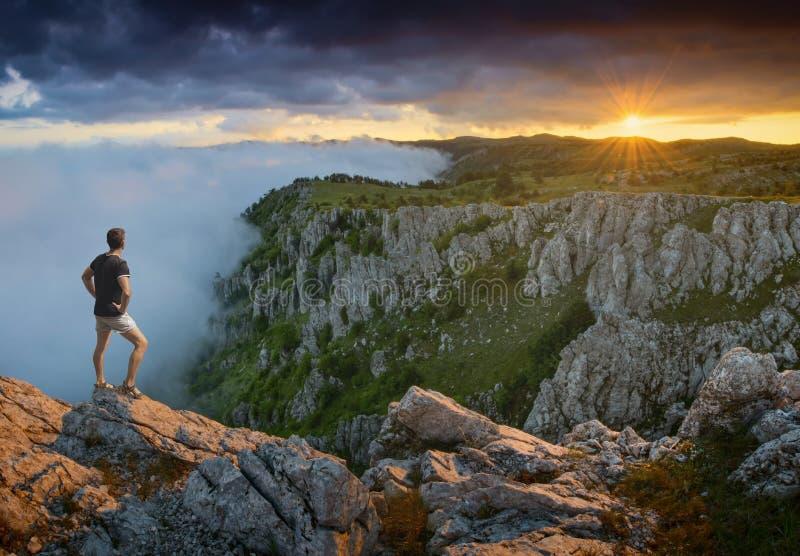 Voyageur se tenant sur un bord de falaises photos stock
