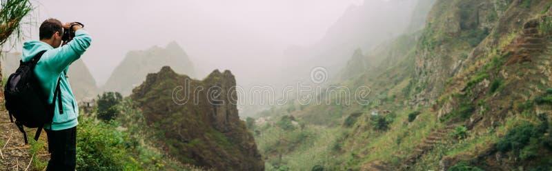 Voyageur supportant l'appareil-photo pour prendre une photo de terrain montagneux raide étonnant avec la vallée luxuriante de can photo libre de droits