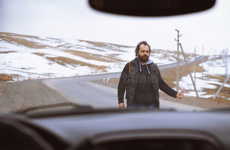 Voyageur sur la route rurale essayant d'arrêter une voiture photographie stock libre de droits