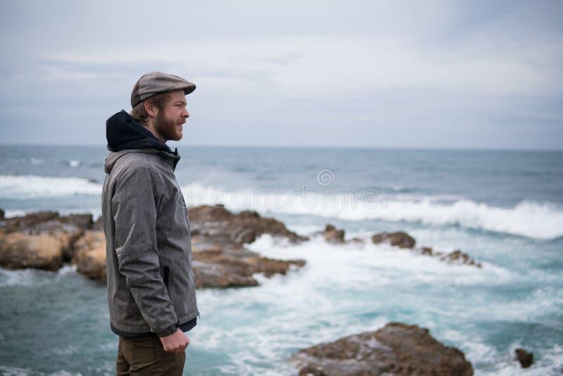 Voyageur sur les roches près de la mer regardant loin l'horizon Rocky Atlantic Ocean Coastline et temps orageux image libre de droits