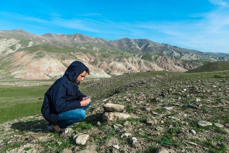 Voyageur tenant une boussole en montagnes photo libre de droits