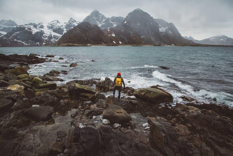 Voyageur utilisant un sac ? dos rouge portant une position rouge de chapeau sur des roches dans la perspective de la mer et des m image stock