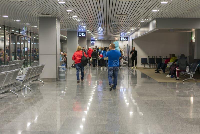 Voyageurs avec des valises marchant par l'aéroport Les passagers marchent par l'aéroport images stock