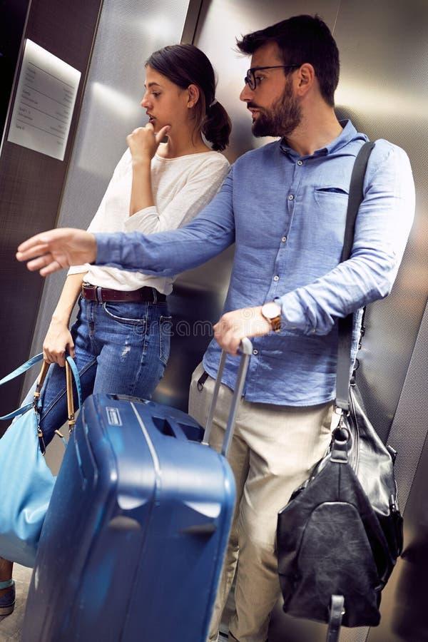 Voyageurs d'homme et de femme avec des valises dans l'ascenseur images libres de droits