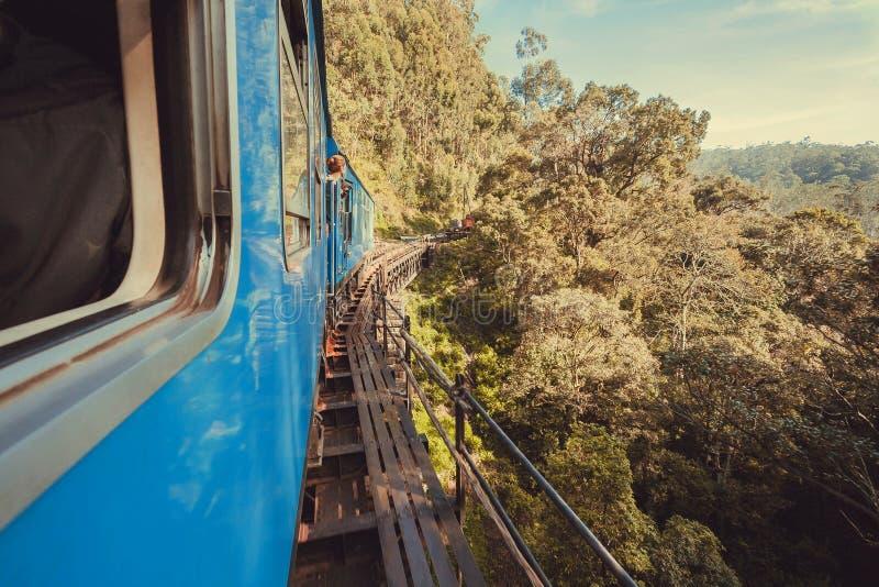 Voyageurs dans le train montant au-dessus du pont au-dessus de la falaise photos stock