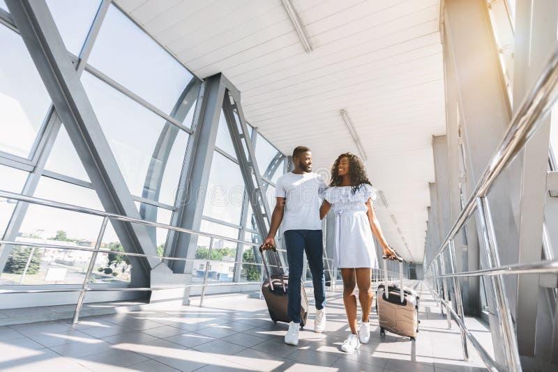 Voyageurs de couples d'afro-américain avec des valises à l'aéroport photographie stock