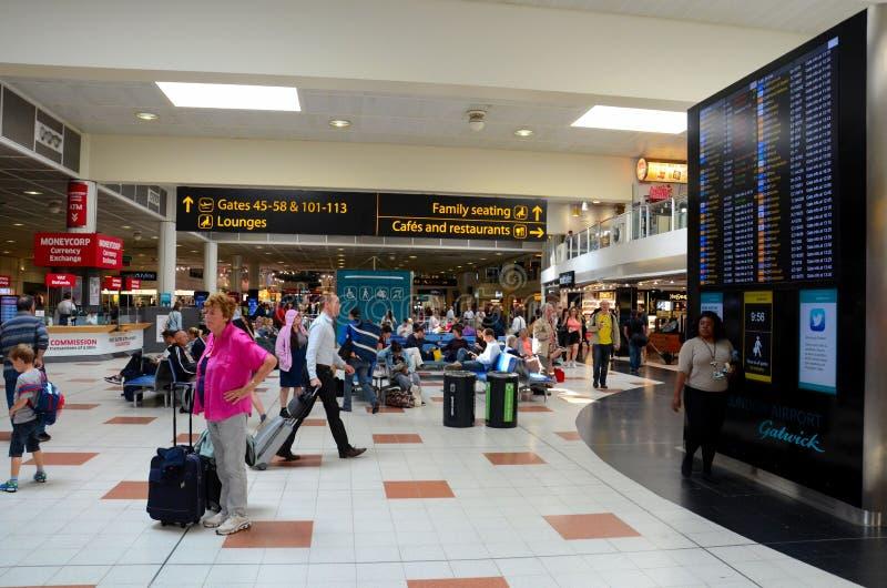 Voyageurs et les gens au salon de départ d'aéroport de Londres Gatwick de l'Angleterre avec l'affichage de vol image libre de droits