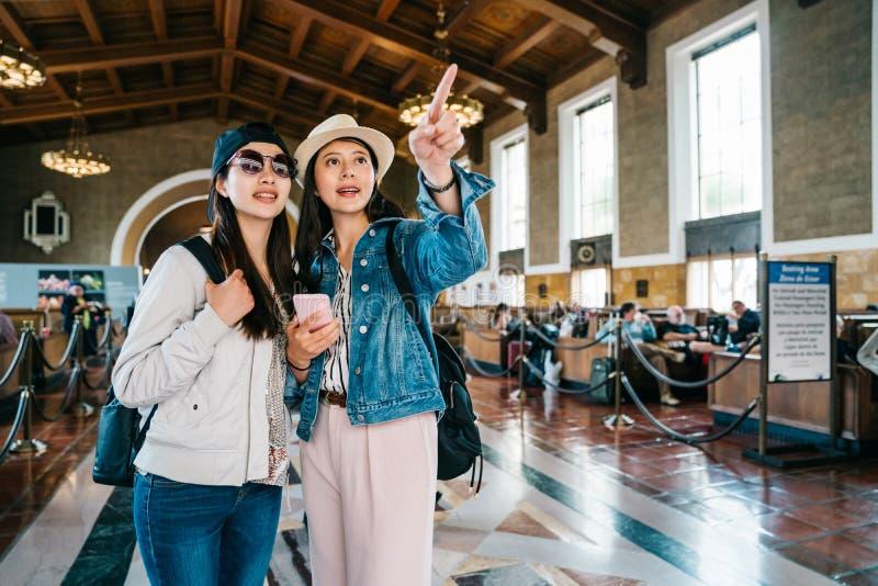 Voyageurs féminins joyeux indiquant le signe photographie stock