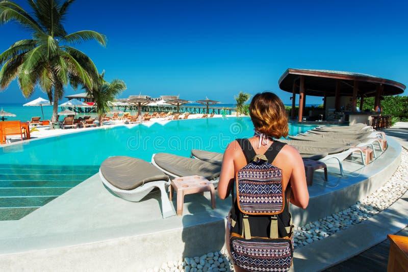Voyageuse de femme avec le sac à dos près de la piscine à l'île tropicale photographie stock libre de droits