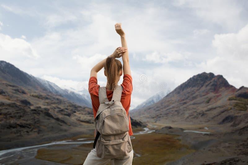 Voyageuse de femme avec un sac à dos, retardant ses mains, supports sur le dessus de la montagne La beauté de la nature, montagne photo libre de droits