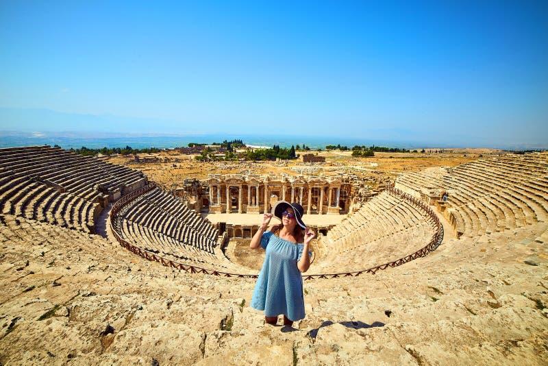 Voyageuse de femme dans le chapeau regardant des ruines stup?fiantes d'amphith??tre dans Hierapolis antique, Pamukkale, Turquie V photographie stock libre de droits
