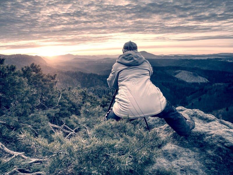 Voyageuse de femme et travail de photographe sur le sommet de roche photographie stock