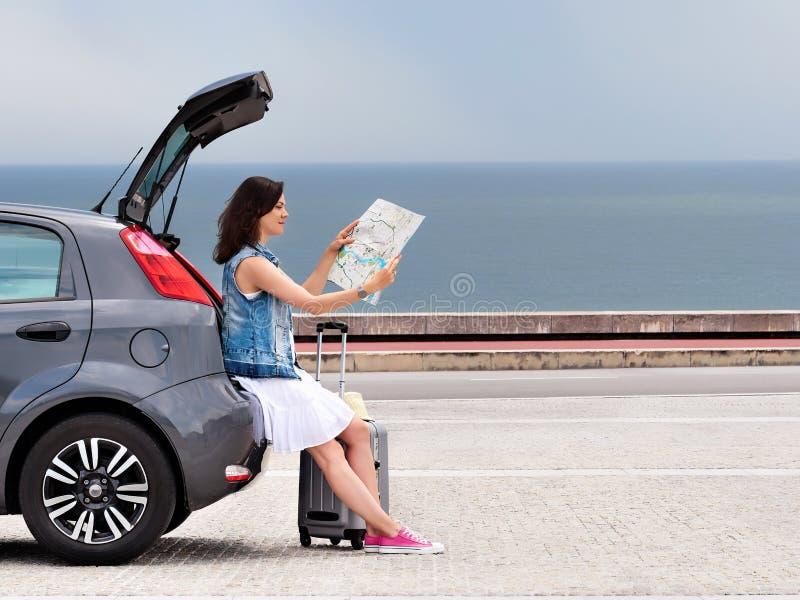 Voyageuse de femme sur la voiture de berline avec hayon arri?re sur la route de bord de la mer image libre de droits