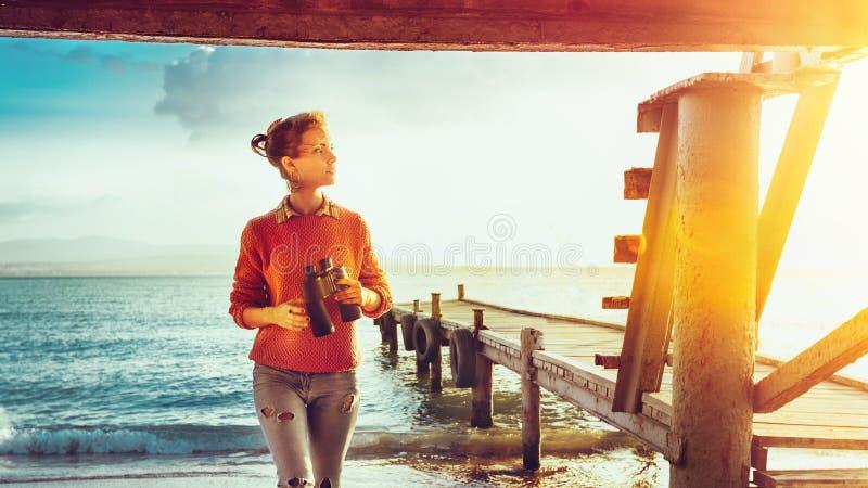 Voyageuse de fille avec des jumelles à disposition se tenant prêt la mer près de P photos stock