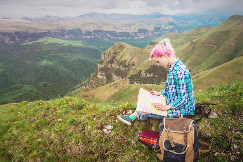 Voyageuse de fille avec les cheveux multicolores se reposant sur la carte et la participation de lecture de nature une boussole à photos libres de droits