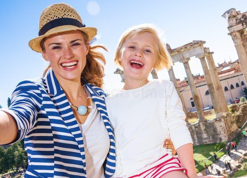 Voyageuses de mère et d'enfant contre Roman Forum prenant le selfie image stock