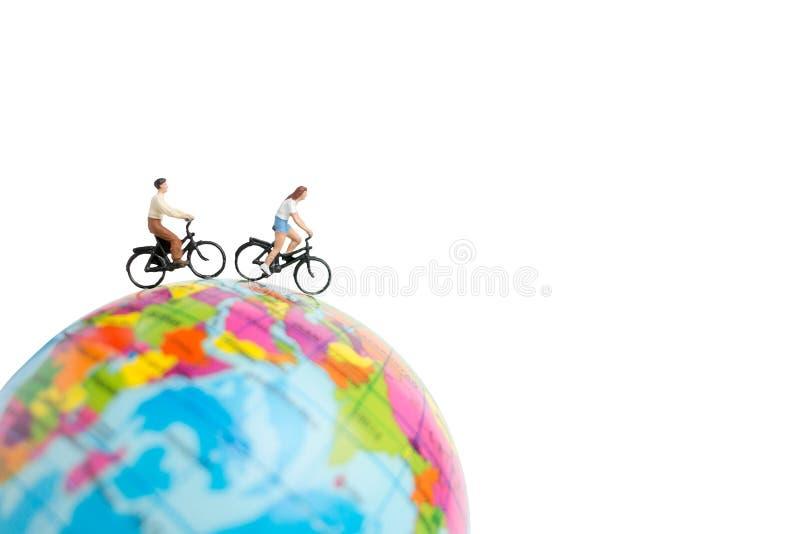 Voyageuses miniatures de personnes avec la bicyclette sur le globe photographie stock libre de droits