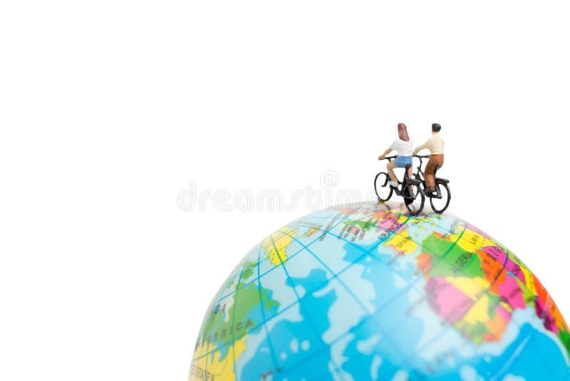 Voyageuses miniatures de personnes avec la bicyclette sur le globe photo libre de droits