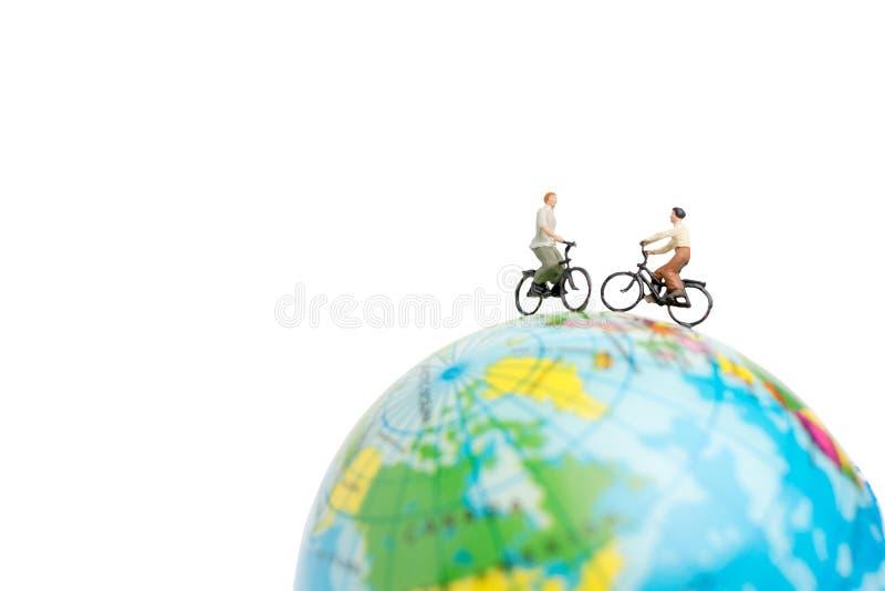 Voyageuses miniatures de personnes avec la bicyclette sur le globe photo stock
