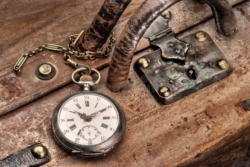 Voyagez avec la montre de poche antique sur une valise en cuir rayée dans la station de train, prête pour partir illustration libre de droits