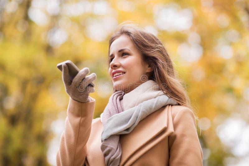 Voz de la grabación de la mujer en smartphone en parque del otoño fotos de archivo