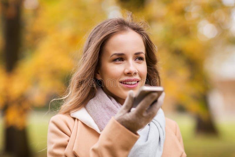 Voz de la grabación de la mujer en smartphone en parque del otoño imagen de archivo