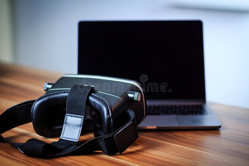 VR-exponeringsglas och bärbar dator på en tabell som symboliserar digitalt lära royaltyfria bilder