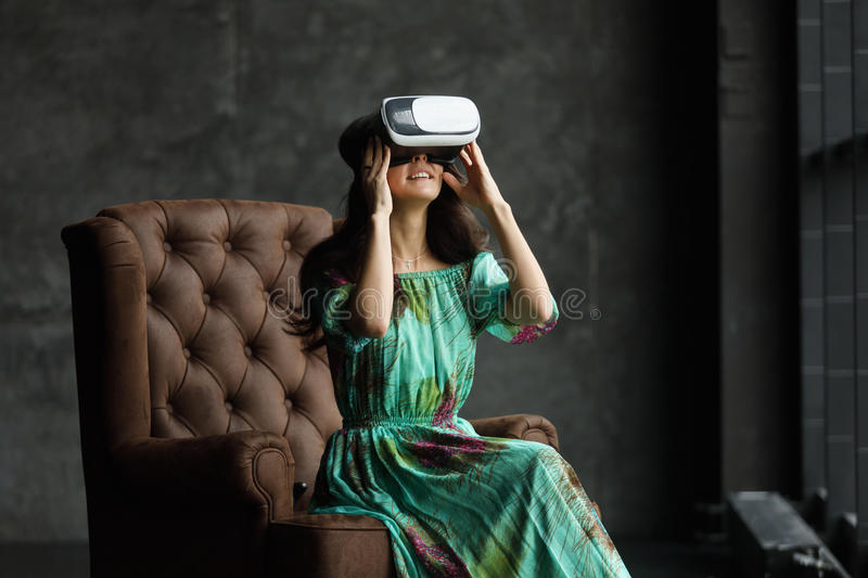 The VR headset design is generic and no logos, Woman with glasses of virtual reality, Sits in a chair, against a dark background. royalty free stock image