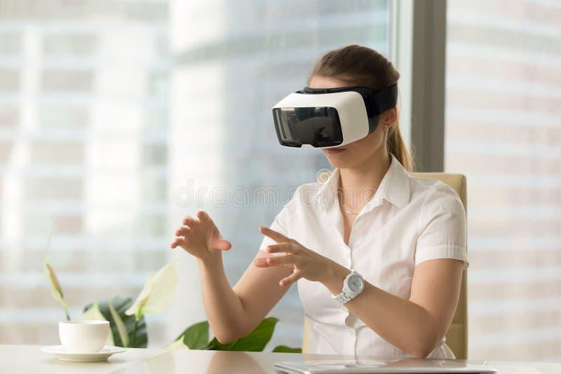 VR-Kopfhörererfahrung, tragende Schutzbrillen der neugierigen Frau, die VI berühren stockfotografie