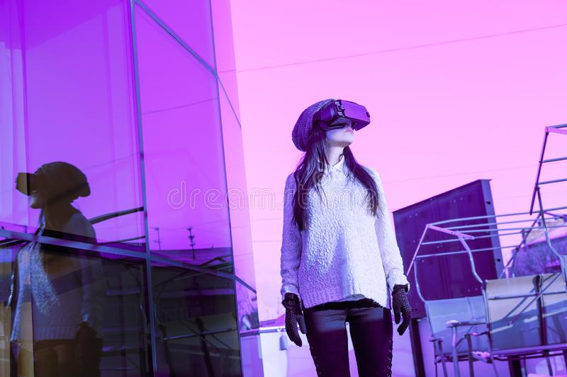 VR pink purple blue girl face woman virtual reality headset brunette phone futuristic violet sky furniture winter. A young girl with a headset on the face meets stock images