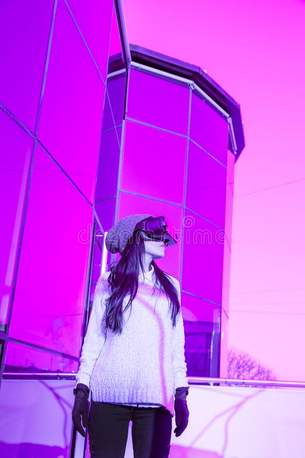 VR pink purple blue girl face woman virtual reality headset brunette phone futuristic violet sky furniture winter. A young girl with a headset on the face meets royalty free stock images