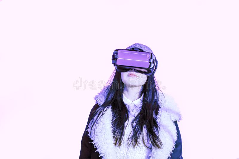 VR pink purple blue girl face woman virtual reality headset brunette phone futuristic violet sky furniture winter. A young girl with a headset on the face meets stock image