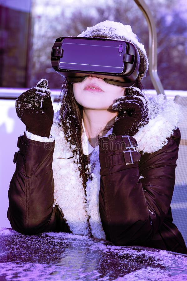 VR pink purple blue girl face woman virtual reality headset brunette phone futuristic violet sky furniture winter. A young girl with a headset on the face meets stock photos
