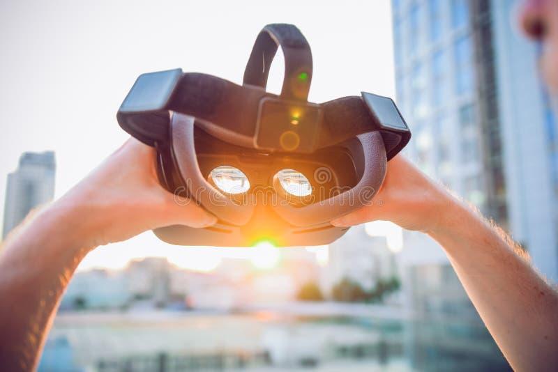VR-skyddsglasögon i manliga händer Man som är klar att bära virtuell verklighetskyddsglasögon Vrhörlurar med mikrofondesignen är  arkivfoton