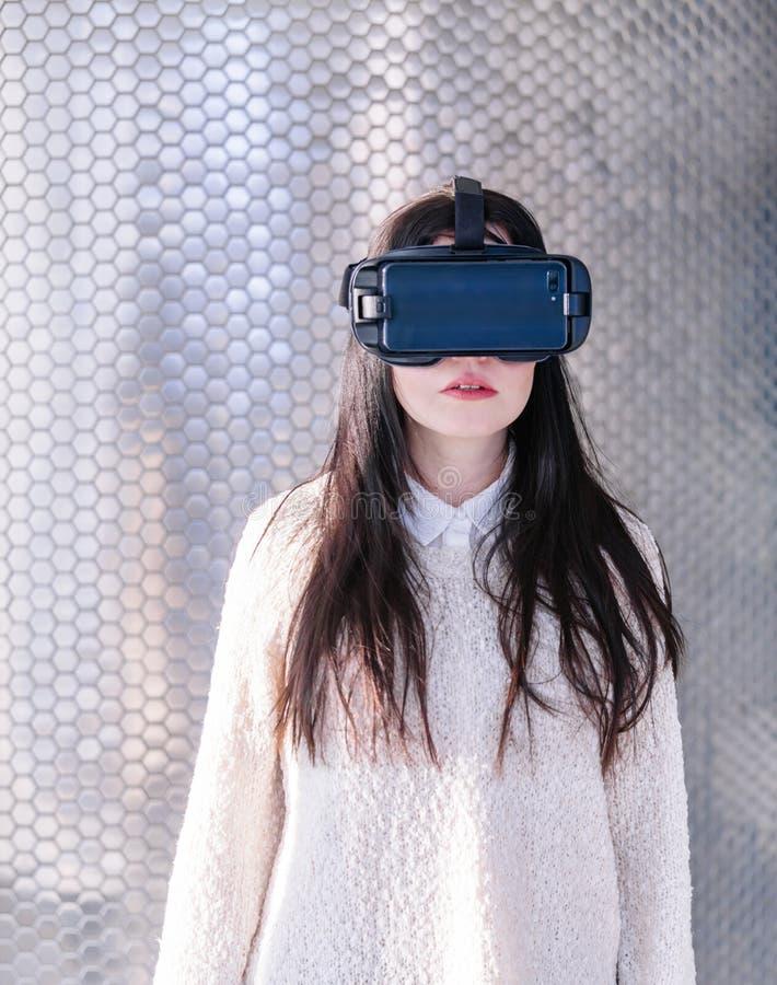 VR Vrouw van de het gezichtstelefoon van het achtergrond de witte bezinningsmeisje virtuele werkelijkheidshoofdtelefoon donkerbru stock afbeelding