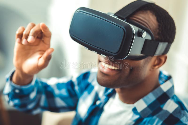 Optimistic young afro american man trying VR. VR world. Enthusiastic afro american man wearing VR headset and smiling royalty free stock photo