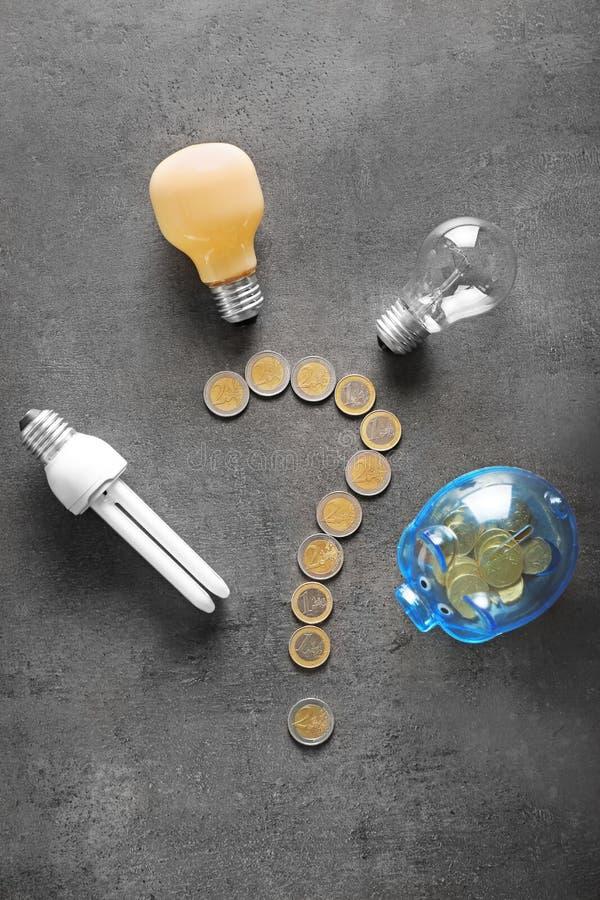 Vraagteken van muntstukken, spaarvarken en gloeilampen op grijze achtergrond wordt gemaakt die Het concept van de elektriciteitsb royalty-vrije stock foto