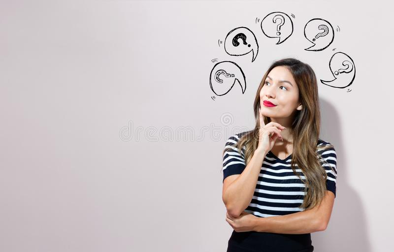 Vraagtekens met toespraakbellen met jonge onderneemster stock afbeeldingen