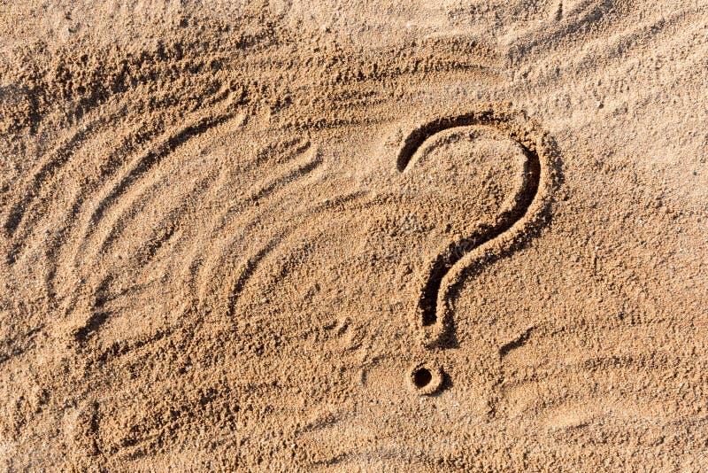 Vraagtekens op strandzand dicht worden uitgewerkt, met exemplaarruimte die stock fotografie