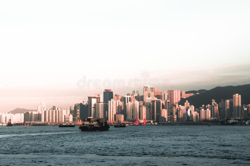 Vrachtschepen die Victoria Harbor in Hong Kong China kruisen tijdens zonsondergang stock afbeelding