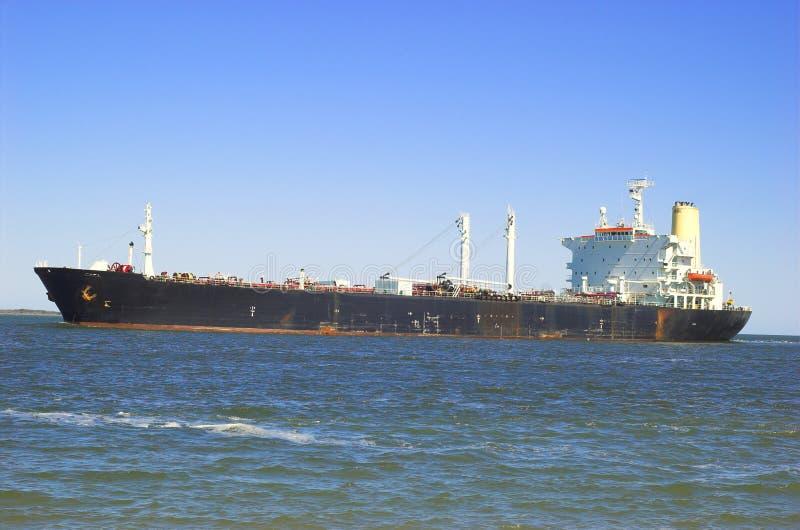 Vrachtschip dat in haven stoomt stock afbeelding